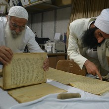 <p>Mr Salim Choheili and Tarmida Sam Zahrooni check Mandaean manuscripts in order to photograph them. In the past, Mandaean priests usually used to copy the manuscripts by hand; however this artwork is time-consuming, and has almost disappeared. Hand copying a sacred manuscript involves much preparation and is considered a sacred activity, bringing good luck and blessing in the Mandaean tradition. There are concerns about preserving Mandaean written literature.&nbsp;</p>