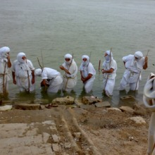 """<p style=""""text-align: center;""""><span>Seven&nbsp;</span><span>priests begin the initiation by baptising each other, then baptising </span><span>Shwalia&nbsp;</span><span></span><span>Anmar</span><span>. The </span><em><strong>Drabsha&nbsp;</strong></em><span>(religious banner, seen to the right of the picture) must be assembled, as this occasion is considered a great sacred event. </span></p>"""