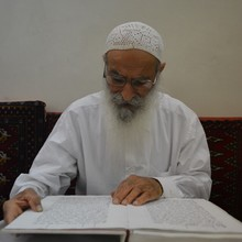 <p>Mr Salem Choheili is a <i>Shkanda</i> (deacon) and highly respected for his learning and teaching. Here he reads from <i>Ginza </i><i>Rba</i><i> - </i><i>Smala</i> (The Mandaean Holy Book – left side), explaining its meaning during a Mandaean women's class in Ahvaz. As one of the few who still speak the Mandaic language, his greatest aim is to help the Mandaeans learn their own language to ensure its survival. He says his biggest concern is that the Mandaeans are not acknowledged in the Iranian Constitution as <i>'</i><i>Ahl</i><i> Al </i><i>Kitab</i> (People of the Book), which has consequences for their existence in Iran.</p>
