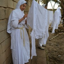 <p>Ms Amal Sabti lives in Ahvaz and works at the Mandaean Cultural Centre there. Here, in preparation for the Parwanaya festival, she checks the white clothes to be worn in the rituals and removes any unwanted small objects.</p>